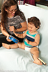 Infant development 12 month old baby boy with mother interested in musical toys hitting tambourine with hands