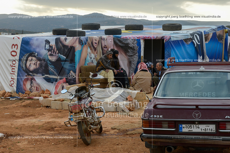 LEBANON Beqaa valley, Deir el Ahmad, camp for syrian refugees, family in tent made from old cinema poster, in front old german Mercedes Benz car / LIBANON Bekaa Tal, Deir el Ahmad, Camp fuer syrische Fluechtlinge am Dorfrand, Familie im Zelt aus alten Kinoplakaten