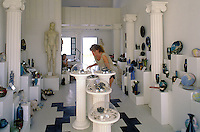 Tourist examines jewelry and other merchandise in arts and crafts store in Oia, north coast of Santorini, Greece.