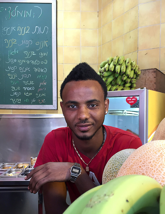 """20. """"African at juice bar"""":  Tel Aviv.<br /> <br /> Many thousands of Ethiopian Jews, as well as other African refugees and asylum seekers, have immigrated to Israel. Yet ongoing discrimination has kept many of them on the periphery of Israeli society. However, this young man seems to have avoided such difficulties, at least on the surface. He is working at a juice bar in Tel Aviv, and looks relaxed and well off with his sporty watch, earing, golden necklace and beatific expression."""