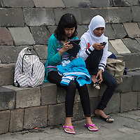 Borobudur, Java, Indonesia.  Two Young Indonesian Girls with Cell Phone and iPad.