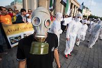 """Protest gegen den syrischen Diktator Bashar al-Assad.<br /> Am Freitag den 21. August 2015 protestierten mehrere hundert Menschen, die meissten Buergerkriegsfluechtlinge aus Syrien, gegen den fortdauernden Buergerkrieg in ihrem Herkunftsland. Sie gedachten annlaesslich des 2. Jahrestag der Opfer des Giftgas-Angriffs vom 21. August 2013 in Damaskus. Das Assad-Regime hatte ueber 1.600 Menschen mit dem Nervengift Sarin ermordet.<br /> Nach Angaben des deutschen Vertreters der """"Syrischen Nationalen Koalition"""", Dr Bassam Abdullah,  werden in Syrien weiterhin Menschen durch Giftgas durch die Regierungstruppen getoetet. Die Koalition ist ein Zusammenschluss von syrischen Muslimen, Christen, Assyrern und Kurden.<br /> Im Bild: Demonstranten haben sich mit Schutzanzuegen bekleidet um gegen die Giftgasangriffe zu protestieren.<br /> 21.8.2015, Berlin<br /> Copyright: Christian-Ditsch.de<br /> [Inhaltsveraendernde Manipulation des Fotos nur nach ausdruecklicher Genehmigung des Fotografen. Vereinbarungen ueber Abtretung von Persoenlichkeitsrechten/Model Release der abgebildeten Person/Personen liegen nicht vor. NO MODEL RELEASE! Nur fuer Redaktionelle Zwecke. Don't publish without copyright Christian-Ditsch.de, Veroeffentlichung nur mit Fotografennennung, sowie gegen Honorar, MwSt. und Beleg. Konto: I N G - D i B a, IBAN DE58500105175400192269, BIC INGDDEFFXXX, Kontakt: post@christian-ditsch.de<br /> Bei der Bearbeitung der Dateiinformationen darf die Urheberkennzeichnung in den EXIF- und  IPTC-Daten nicht entfernt werden, diese sind in digitalen Medien nach §95c UrhG rechtlich geschuetzt. Der Urhebervermerk wird gemaess §13 UrhG verlangt.]"""