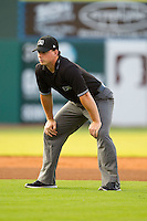 Umpire Ryan Benson handles the calls on the bases during the South Atlantic League between the Charleston RiverDogs and the Greensboro Grasshoppers at NewBridge Bank Park on July 17, 2013 in Greensboro, North Carolina.  The Grasshoppers defeated the RiverDogs 4-3.  (Brian Westerholt/Four Seam Images)