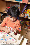 Education Preschool 3-5 year olds art activity boy gluing pieces on a model of his house vertical