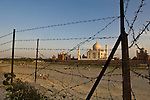 The Taj Mahal and barbed wire fence from the opposite bank of the Yamuna River. Agra, India.