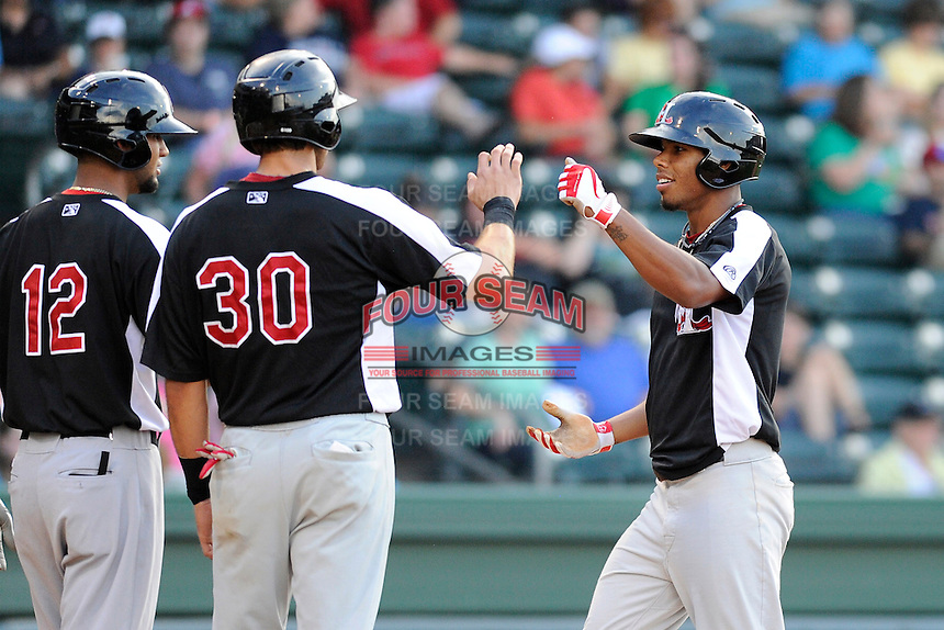 Outfielder Nick Williams (1) of the Hickory Crawdads, right, is congratulated after hitting a home run by Noman Mazara (12) and Joey Gallo (30) in a game against the Greenville Drive on Friday, June 7, 2013, at Fluor Field at the West End in Greenville, South Carolina. Williams is the No. 25 prospect of the Texas Rangers, according to Baseball America and was a second-round pick in the 2012 First-Year Player Draft. Greenville won the resumption of this May 22 suspended game, 17-8. (Tom Priddy/Four Seam Images)