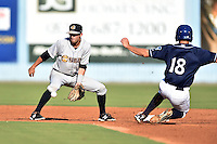 Charleston RiverDogs shortstop Tyler Wade #7 fields the ball and attempts to apply the tag to a hard sliding Michael Benjamin #18 during a game against the Asheville Tourists at McCormick Field July 26, 2014 in Asheville, North Carolina. The RiverDogs defeated the Tourists 8-7. (Tony Farlow/Four Seam Images)
