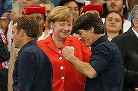 Germany manager Joachim Low gives a congratulatory fist pump towards Germany Chancellor Angela Merkel