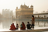 Amritsar, Punjab, India.  The Golden Temple - Harmandir Sahib - at dawn with an old Sikh man greeting a family sitting cross-legged at the side of the lake.