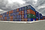 Shipping containers stacked high against storm clouds.