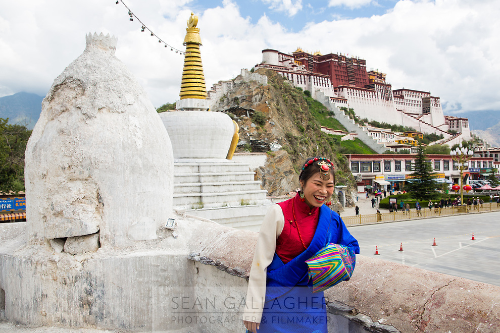 A woman laughs as she poses for pictures near the Potala Palace, in the Tibetan capital of Lhasa.