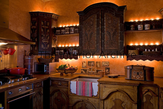 The kitchen has bespoke carved and hand-painted cupboards and shelves