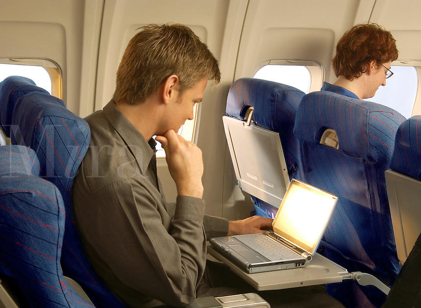 Airplane passenger with laptop.
