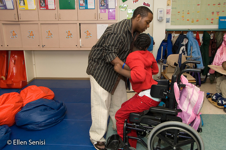 MR / Albany, NY.Langan School at Center for Disability Services .Ungraded private school which serves individuals with multiple disabilities.Teaching assistant (African-American) lifts child out of wheelchair. Student is wearing a diaper. Like many people with CP, her muscles are not capable of allowing her to manage her toileting independently. Girl: 10, African-American, cerebral palsy, expressive and receptive language delays.MR: And6; Wes2.© Ellen B. Senisi