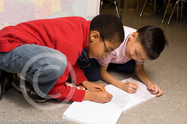Education Elementary Grade 3 two boys working on notebooks, writing
