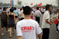 """A man wearing a nationalist shirt that says """"China's Voice"""" walks through the crowd of spectators during the Nanjing, China, leg of the 2008 Olympic Torch Relay.  ."""