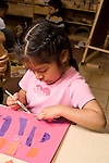 Education preschoool children ages 3-5 art activity girl gluing pieces of paper torn paper collage vertical