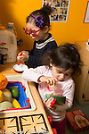 Preschool program toddler-age 2 two girls playing separately in pretend play area cooking