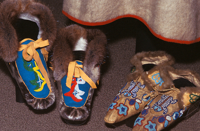 Two pair of Tlingit beaded moccasins edged with animal fur. One pair is made from seal and the other is from animal hide