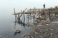 """A polluted beach in the bay of Jakarta. According to the the Climate Reality Project, """"without flood protection measures, sea level rise could expose up to 6 million Indonesians to annual coastal flooding. The worst of the flooding would occur on the island of Java, where Jakarta is located."""""""