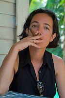 Woman smoking a freshly rolled Cuban cigar, Vinales, Pinar del Rio Province, Cuba.