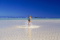 Woman running on sunny sand bar surrounded by ocean