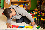 Education Preschool boy playing with plastic duplo bricks and human figure talking to himself as he plays