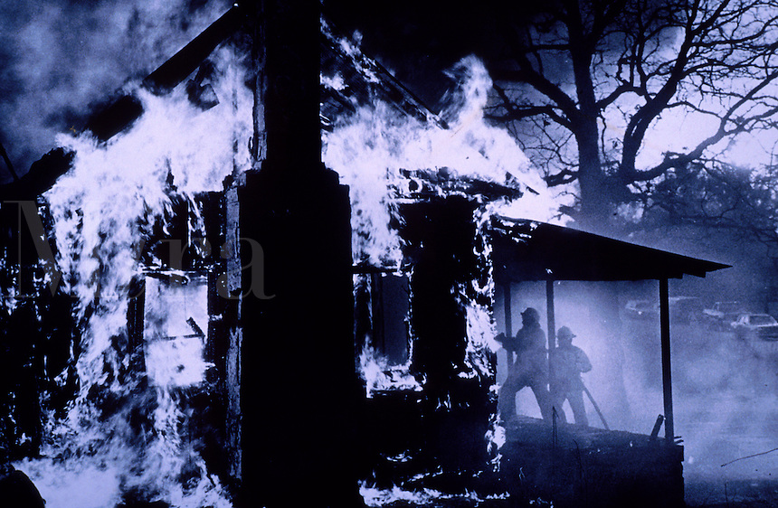 Firefighters approach a burning building.
