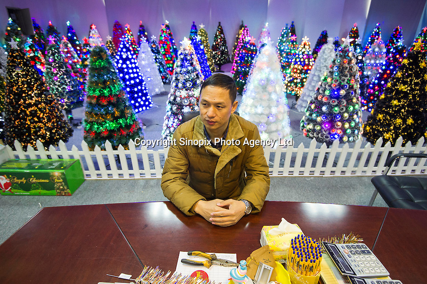 November 28, 2015, Yiwu China - Reng Guoan (English name Raven) General Manager  of Sinte An Christmas tree factory sits at a desk in his factory showroom. His company makes one million artificial trees a year for export and around 100,000 of those go to the UK.Photo by Dave Tacon / Sinopix