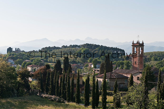 The view over the village of Massa Macinaia towards the Carrara mountains from the gardens of the Villa Massei in Lucca