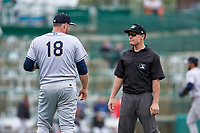 Umpire Bobby Tassone talks to first baseman Zack Shannon (18) between innings of a Midwest League game between the Kane County Cougars and Fort Wayne TinCaps at Parkview Field on May 1, 2019 in Fort Wayne, Indiana. Fort Wayne defeated Kane County 10-4. (Zachary Lucy/Four Seam Images)