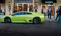 A young man admires a Lamborghini parked at a suburban mall during teh Christmas shopping season.