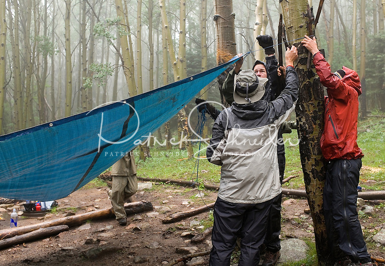 Photo story of Philmont Scout Ranch in Cimarron, New Mexico, taken during a Boy Scout Troop backpack trip in the summer of 2013. Photo is part of a comprehensive picture package which shows in-depth photography of a BSA Ventures crew on a trek. In this photo BSA Ventures crew members work together in the heavy rain to string up a plastic tarp over the campsite cooking area.  at Philmont Scout Ranch.   <br /> <br /> The  Photo by travel photograph: PatrickschneiderPhoto.com