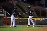 Salem-Keizer Volcanoes center fielder Aaron Bond (51) is congratulated by manager Hector Borg (13) after hitting a home run during a Northwest League game against the Eugene Emeralds at Volcanoes Stadium on August 31, 2018 in Keizer, Oregon. The Eugene Emeralds defeated the Salem-Keizer Volcanoes by a score of 7-3. (Zachary Lucy/Four Seam Images)