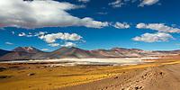 Colorful Salar de Aguas Calientes landscape with the lagoon and Láscar Volcano under a blue sky with white clouds, San Pedro de Atacama, Chile