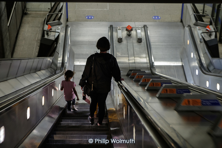 Mother and child on an escalator at Waterloo tube station, London, on the day after the August bank holiday.