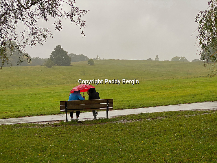 Couple sitting in the rain under a red umbrella on Hampstead Heath, North London.<br /> <br /> Stock Photo by Paddy Bergin