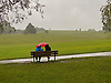 Couple sitting in the rain under a red umbrella on Hampstead Heath, North London.<br />
