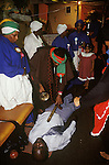 """Mount Zion Spiritual Baptist church North London. Bishop Noel in red and green turban, places a spirit wand, and rings a bell over the body of a man in a trance so as to drive out evil spirits, exorcises them from his body."""" 1990s"""