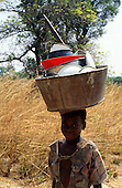 Zambia, Africa. Smiling young girl carrying a metal wash basin on her head full of clean pots and plates; Chambeshi.