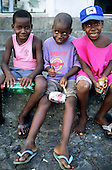 Rio de Janeiro, Brazil. Three young boy from poor families using plastic bottle, tin can and lollipop sticks as drums.