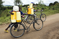 Rwanda. Southern province. Rugobagoba village. View on the hills. Two young black boys push their bicycles up the hill on a dirt road. They both work and carry yellow plastic containers fully loaded with fresh milk.  One of thekids has a smile on his face.  © 2007 Didier Ruef