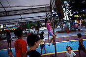 A young Filipino youth climbs to fix the move the makeshift basketball post before their game at the Remedios circle in Malate, Manila in Philippines. Photo: Sanjit Das