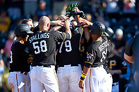 Pittsburgh Pirates first baseman Edwin Espinal (79) is mobbed by his teammates after hitting a game-winning three-run home run during a Spring Training game against the Tampa Bay Rays on March 10, 2017 at LECOM Park in Bradenton, Florida.  Pittsburgh defeated New York 4-1.  (Mike Janes/Four Seam Images)