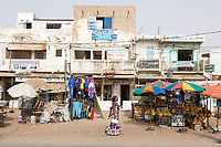 Senegal, Touba.  Street Scene, Woman Walking Past Clothing and Fruit Stands.