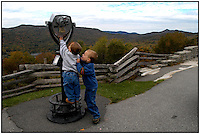 Two boys work to get tall enough to look through the binoculars at Grandfather Mountain, in Avery County, NC. Grandfather Mountain is a popular mountain and state park located near Linville, North Carolina. It is the highest peak in the eastern escarpment of the Blue Ridge Mountains. Boys are model released.