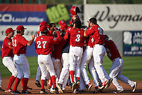 Auburn Doubledays players including Kevin Mooney (33), Victor Robles (27), Telmito Agustin (3), Jake Jefferies (23), Melvin Rodriguez (16) mob Diomedes Eusebio (31) after a walk off base hit during a game against the Batavia Muckdogs on September 7, 2015 at Falcon Park in Auburn, New York.  Auburn defeated Batavia 11-10 in ten innings.  (Mike Janes/Four Seam Images)