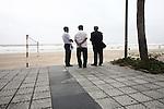 Men watch a winter storm brewing offshore in Da Nang, Vietnam. Dec. 23, 2012.