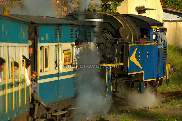 """Nilgiri Mountain Railway pulled by it's steam engine """"Nilgiri Queen"""" on it's descent from Coonoor to Mettupalayam. Part of the journey is managed only by a rack-and-pinion system. India, Tamil Nadu. --- Info: The Nilgiri Mountain Railway (NMR) is the only rack railway in India and connects the town of Mettupalayam with the hill station of Udagamandalam (Ooty), in the Nilgiri Hills of southern India. The construction of the 46km long meter-gauge singletrack railway in Tamil Nadu State was first proposed in 1854, but due to the difficulty of the mountainous location, the work only started in 1891 and was completed in 1908. This railway, scaling an elevation of 326m to 2,203m and still in use today, represented the latest technology of the time. In July 2005, UNESCO added the NMR as an extension to the World Heritage Site of Darjeeling Himalayan Railway."""