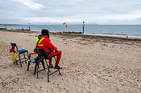 BNPS.co.uk (01202 558833)<br /> Pic: MaxWillcock/BNPS<br /> <br /> Pictured: An RNLI lifeguard watches over the empty beach with the mass of rotten seaweed.<br /> <br /> A south coast beach has become a no-go zone at the height of the summer holidays after a mass of rotten seaweed was allowed to fester on the sand.<br /> <br /> The vast carpet of kelp has been left to gather on Avon Beach in Christchurch, Dorset, for over a month.<br /> <br /> The unpleasant mess is attracting flies and is putting people off visiting the beauty spot which is normally hugely popular with families.<br /> <br /> Bathers are having to wade through the sticky seaweed to get to the sea and are usually left with their legs covered in it.